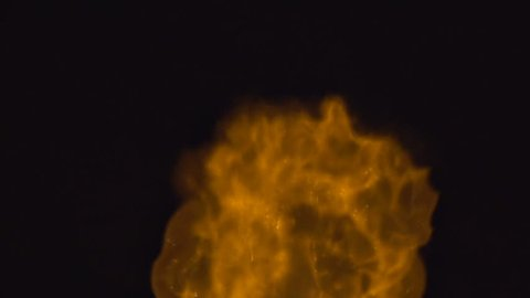 Close slow motion shot of a strange gaseous cloud of burning flames rolling upwards with particulates glowing.