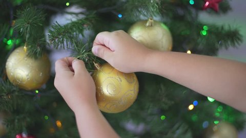Great close-up macro shot of cute happy child hand putting a shiny golden Christmas ball on the Christmas tree. Kid decorating Christmas tree. Holidays.