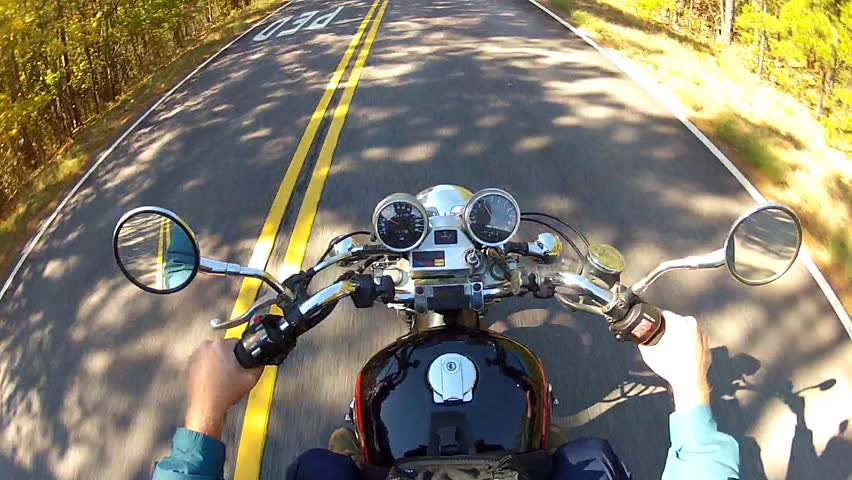 A shot of the handlebars, gages and gas tank of a speeding motorcycle as seen
