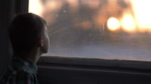 boy rides on a train in the evening looks out the window