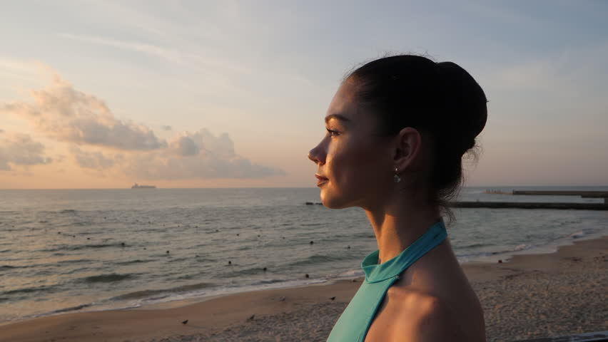 Portrait of young attractive woman with brunette hair standing near sea or ocean in sunrise or sunset light. The girl looks at the sun. Slow motion. Gimbal shot. #31129117