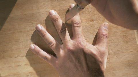 Dangerous game stabbing knife between fingers