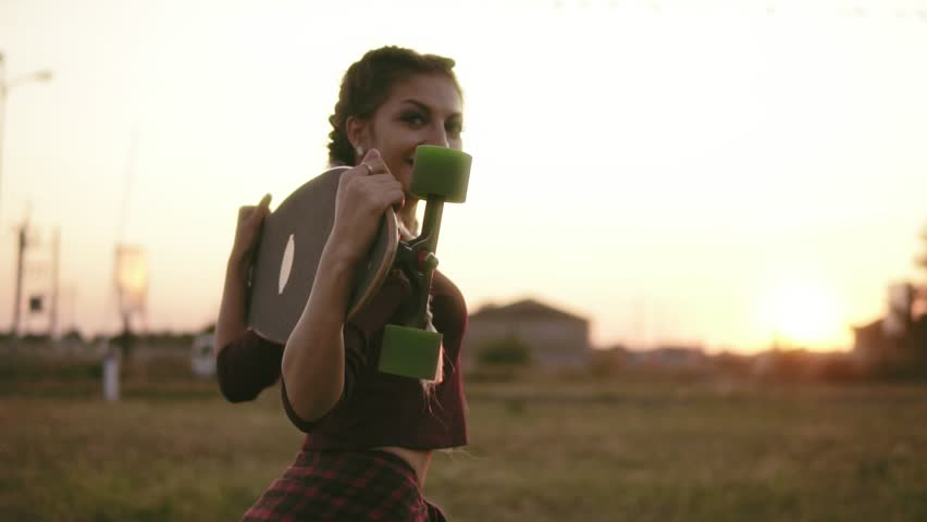 Back view of woman in plaid shirt and tank top holding longboard and walking during the sunset in summertime. Lens flare. Slowmotion shot