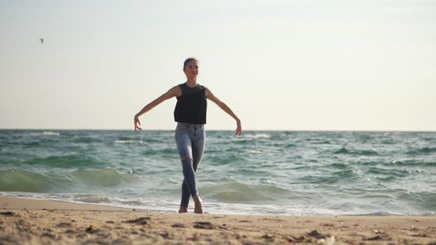 Young woman in casual style - denim and black top doing ballet at the beach. Attractive ballerina practices in hands exercises on sandy plage in autumn. Slow motion. Sea waves background