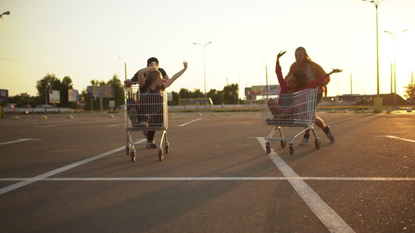 multiethnic friends entertaining in mall parking lot in bright day racing with shopping cart enjoying free time slomo