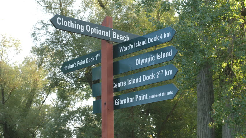 Toronto Islands sign including directions to clothing optional nude beach. Handheld shot with stabilized camera.
