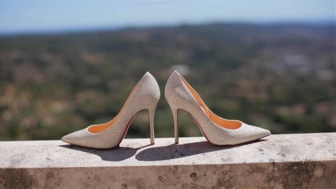 49bae4ba2f3 Woman shoes close up louboutins at green summer landscape shallow dof.  beautiful pair of stylish luxury bridal high-heeled white stiletto of  material shining reflecting sun stand on balcony or terrace