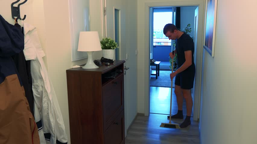 A young man sweeping the floor in the apartment  | Shutterstock HD Video #31186603