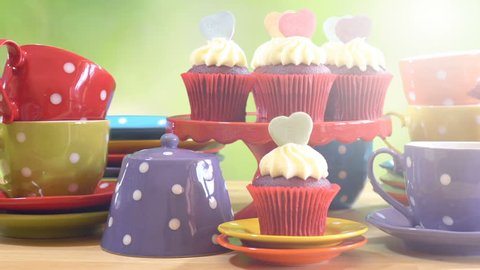 Colorful Mad Hatter style tea party with cupcakes and rainbow colored polka dot cups and saucers, with bokeh garden background and lens flare, panning across close up.