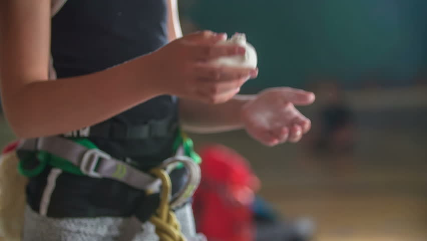 A young student is trying to put some climbing chalk on her hands. She is about to start climbing on the climbing wall.