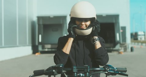 Attractive Caucasian female biker sitting on a motorcycle, putting on protective helmet. 4K UHD 60 FPS
