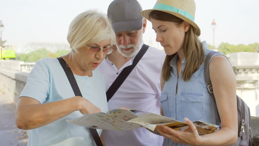PARIS, FRANCE- CIRCA August 2017: Happy family enjoying vacation together. Seniors and their young daughter studying city map looking for showplaces. Lost in city looking for directions | Shutterstock HD Video #31212907