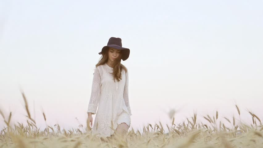 View from below of young pretty woman in white dress and black hat walking in the field