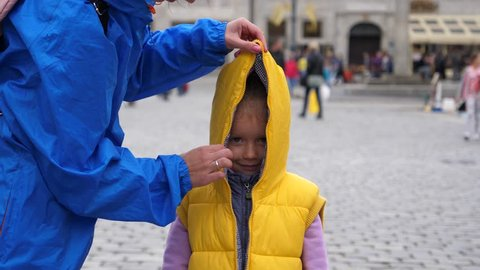 Little Kid Girl Have Fun Playfully Appear Opening Up Zipper Of Sleeveless Jacket With A Hood
