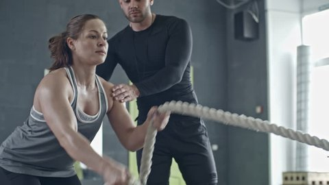 Muscular woman doing battle rope exercise in cross training gym with help of personal coach