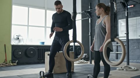 Slowmo shot of personal cross training coach showing athletic woman how to do kettlebell snatch in gym