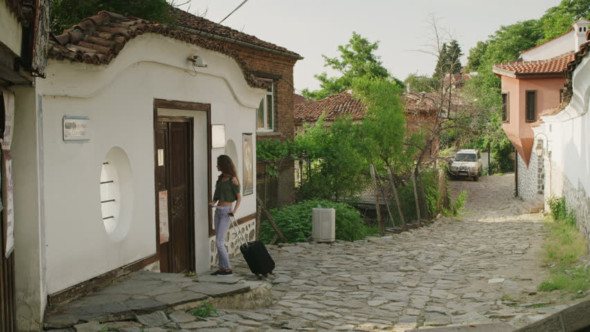 Wide slow motion shot of woman with suitcase knocking on door of house / Plovdiv, Bulgaria