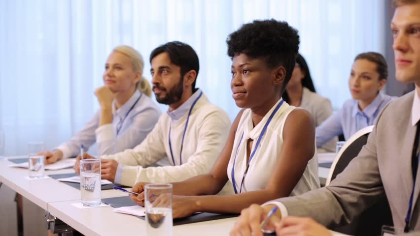 Business and education concept - group of people listening and taking notes at international conference | Shutterstock HD Video #31241827