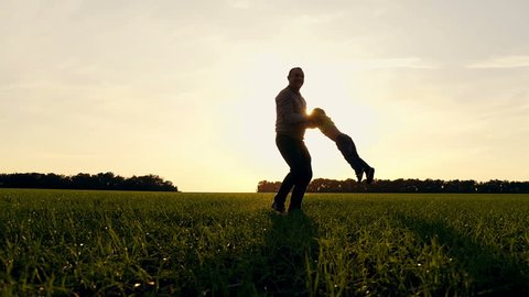 Happy father and son playing nature in the park at sunset. Father keeps his son by the hands and turns with him. Slow motion.