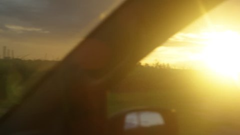 A shot from a car showing a beautiful sunset seen on top of a beautiful landscape.