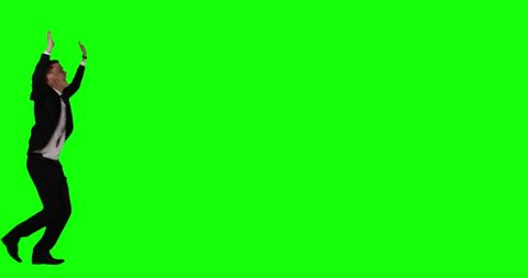 Scared businessman run away while screaming and raise hands in the studio against green screen background. Shot in 4k resolution