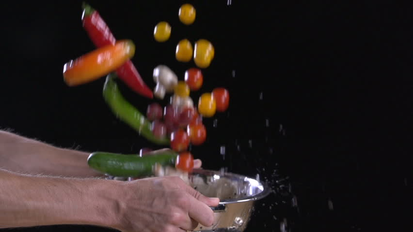 Fresh food. Super slow motion. Fruit and vegetables flying out of colander with water drops.  Multi colored shot on a black background. Man's hand  washes food. Food footage. 200 fps. 05