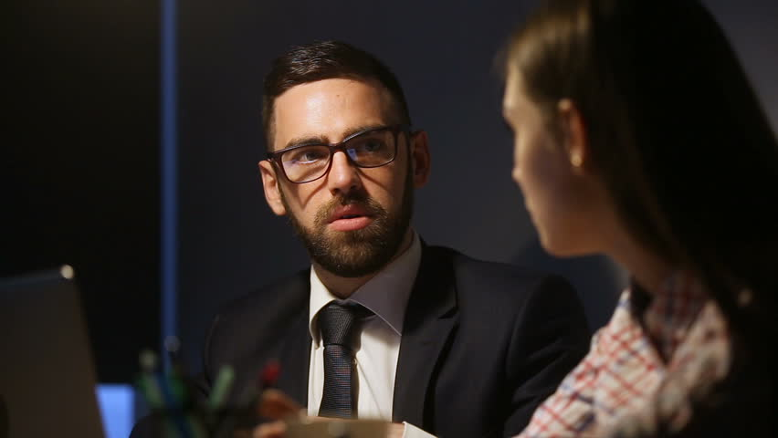 Serious businessman in suit and glasses discussing explaining business project to businesswoman, team of two businesspeople working late together in lamplight, partners talking sitting at office desk