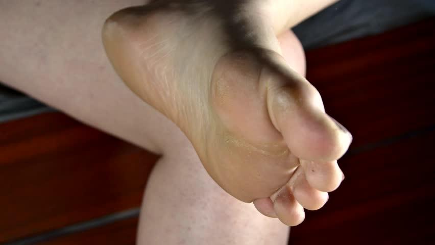 Young Woman Tending Her Foot, Polishing Callused Heel Using A Heel Polisher