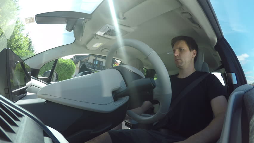 CLOSE UP: Man in innovative autonomous automated electric car using self-parking autopilot for parallel parking on street. Computer in autopilot mode turning wheel, moving vehicle on parking spot