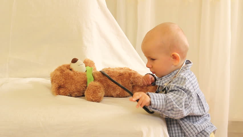 Little cute baby playing as doctor with its teddy bear toy