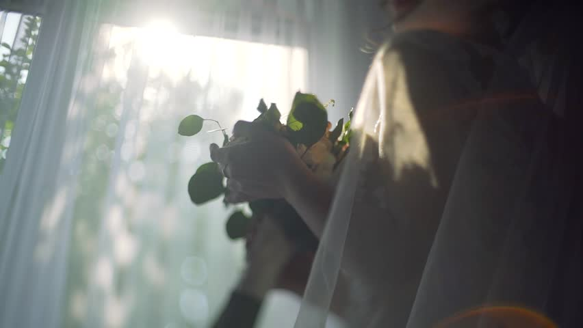 Bride holds wedding bouquet in Hands while staying on the backround of the window. Close up. near Sunlight.