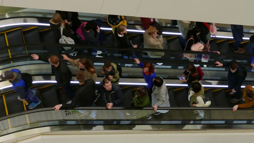 MINSK, BELARUS - APR 9, 2017: Ungraded: People on escalators. Buyers are moving on escalators inside a multi-storey shopping center. Ungraded H.264 from camera without re-encoding. (av38053u)