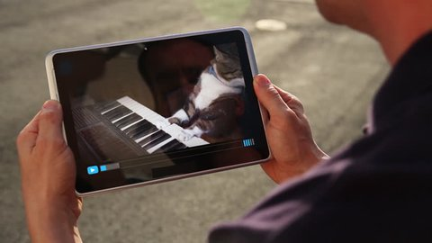 A man holding a tablet PC watches a viral video of a funny cat playing a keyboard or electric organ.