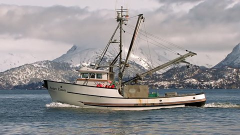 HOMER, AK - CIRCA 2012: An Alaskan trawler returns to port just off the Homer Spit, with the resplendent Kenai Mountains looming in snow-covered glory beyond the azure waves of Kachemak Bay.