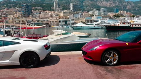 Monaco-Ville, Monaco - June 22, 2017: Two Luxurious Italian Supercars Parked on Port Hercule: White Lamborghini Aventador LP700-4 and Red Ferrari California - 4K Video