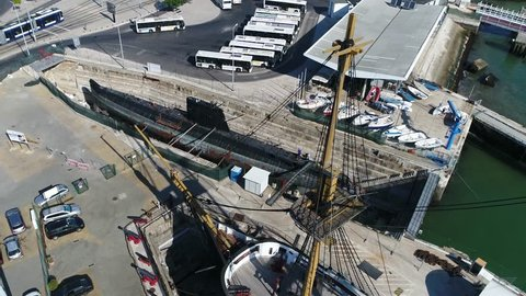 Aerial bird-eye view of submarine in empty dry dock used for construction maintenance and repair of several watercraft submarine is of small class and in port because of repair and maintenance of ship