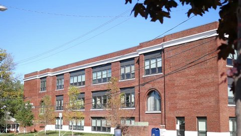 An outdoor afternoon establishing shot of a red brick school building in early fall