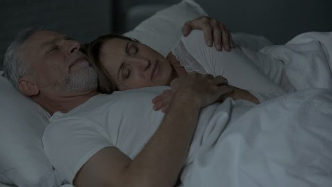 Old couple sleeping in bed, lady lying on male chest, man holding arm around her
