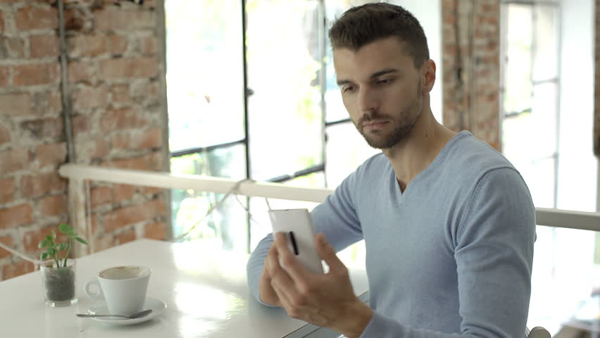 Handsome man in blue sweater doing selfies on smartphone in the bistro, steadycam shot  | Shutterstock HD Video #31431337