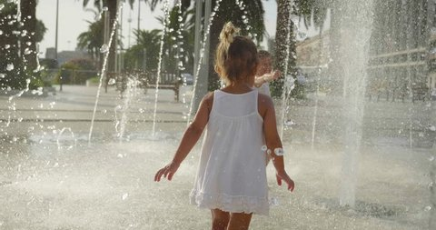 little girls in town play with water in the fountains, happy and carefree, concept of freedom and happiness in childhood, starting summer and tourist cities.