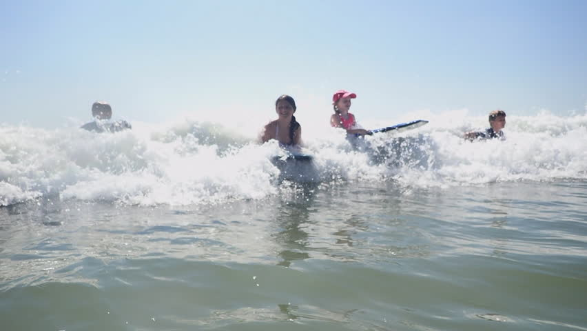 Children Bodyboarding In Ocean Waves At Myrtle Beach SC Vacation