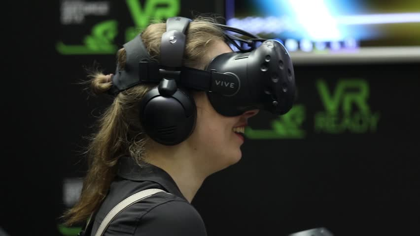 Moscow, Russia - September, 2017: Girl playing virtual reality game in HTC Vive VR headset with accessories controllers on IGROMIR (Games World) and Comic Con Russia 2017 in Moscow, Russia | Shutterstock HD Video #31455967