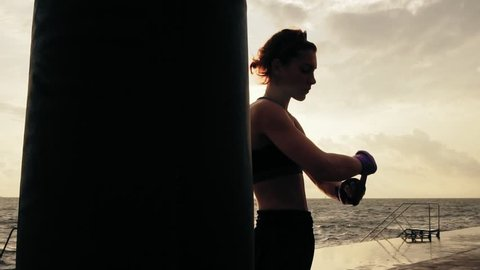 Camera round movement: female boxer wrapping hands with boxing wraps on the beach by the ocean standing against the sun. Lens flare