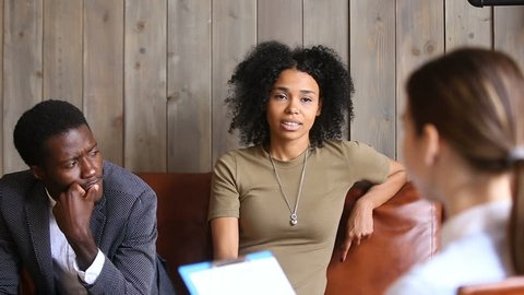 African couple sitting on couch at psychologists, black unhappy woman sharing marital problems talking to white counselor holding clipboard, family marriage counseling therapy session concept