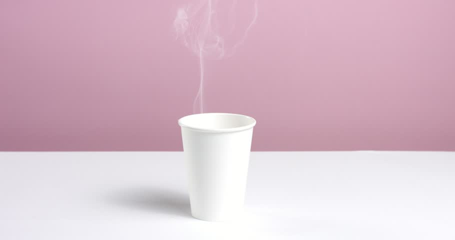 Hot water or coffee poured into a plain unlabeled paper cup on white table against pink wall, steam rising | Shutterstock HD Video #31540177