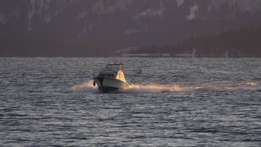 HOMER, AK - CIRCA 2011: A small cabin cruiser fishing boat blasting its way through small waves as the sun sets.