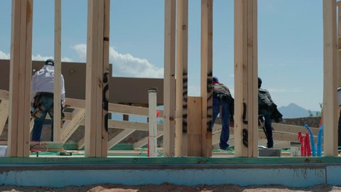 Construction Workers Lift Framed Wall Into Place. view moves right as construction workers lift a framed wall into place for residential home construction