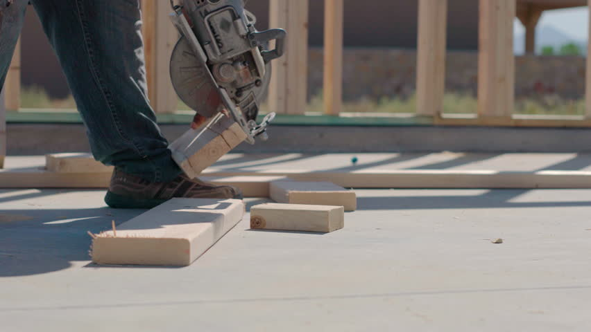 Worker Cuts Wood Partial Using Foot as Leverage. a construction worker quickly cuts wood using his foot as leverage.