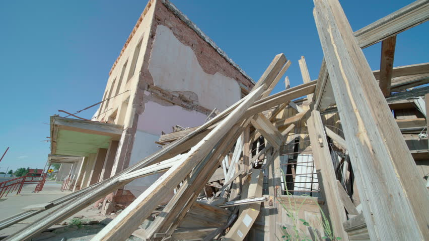 Rubble and Abandoned Building Move Left Low Angle. view moves left on a low angle perspective of rubble from a destroyed building with an abandoned building next door in the background