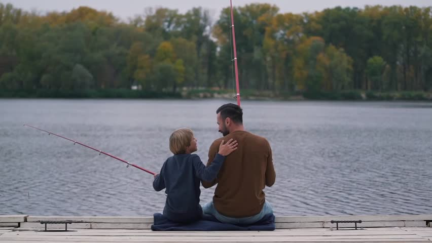 Dad encourages his son on fishing. | Shutterstock HD Video #31551157